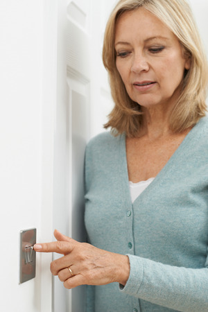 turning off: Mature Woman Turning Off Light Switch At Home