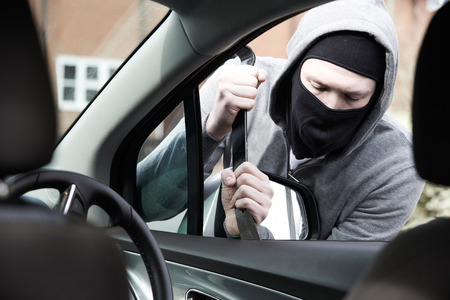 crowbar: Masked Man Breaking Into Car With Crowbar Stock Photo