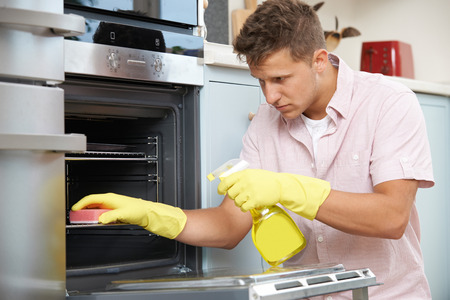 are fed: Fed Up Woman Cleaning Oven At Home Stock Photo