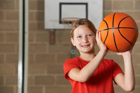 Girl Shooting Basketball In School Gym Stock Photo
