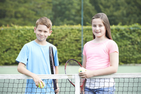 Portrait Of Boy And Girl Playing Tennis Together