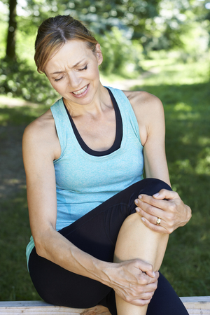 whilst: Woman With Sports Injury Sustained Whilst Exercising Outdoors