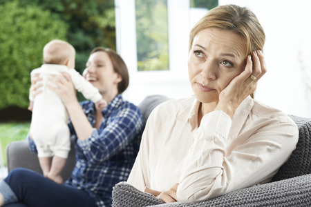 Sad Mature Woman Jealous Of Mother With Young Baby Stock Photo