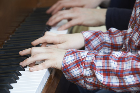 duet: Close Up Of Boy Playing Piano Duet With Teacher