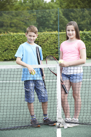 10 years old: Portrait Of Boy And Girl Playing Tennis Together