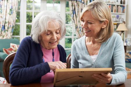 neighbor: Senior Woman Looks At Photo In Frame With Mature Female Neighbor Stock Photo