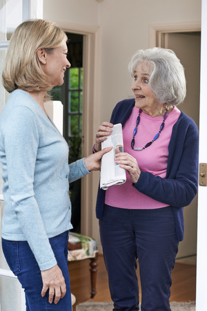 Woman Delivering Newspaper To Elderly Neighbour Stock Photo