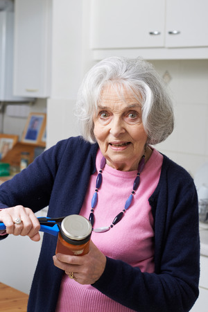 lid: Senior Woman Taking Lid Off Jar With Kitchen Aid Stock Photo