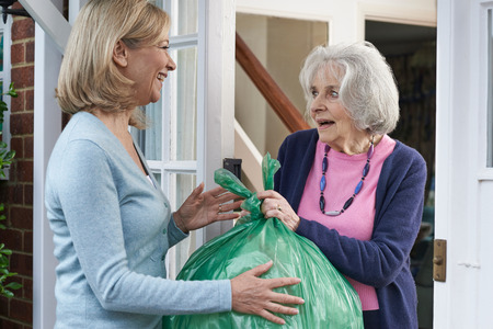 Woman Taking Out Trash For Elderly Neighbour Stock Photo