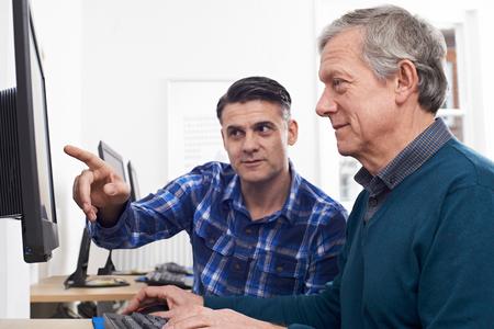 evening class: Tutor Helping Mature Man In Computer Class