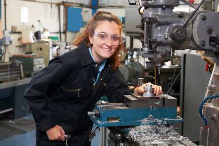 machinist: Female Apprentice Engineer Working On Drill In Factory Stock Photo