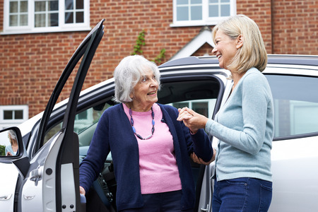 Female Neighbor Giving Senior Woman A Lift In Car Archivio Fotografico