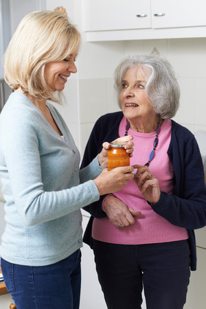 neighbor: Woman Helping Senior Neighbor To Remove Jar Lid Stock Photo