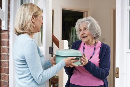 senior women: Woman Bringing Meal For Elderly Neighbour Stock Photo