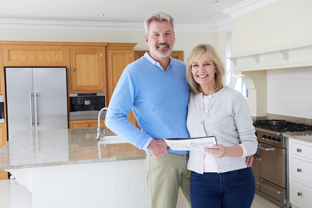 property ladder: Mature Couple Looking Around Kitchen Of House For Sale
