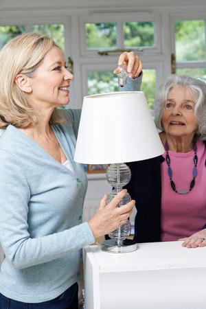 neighbor: Female Neighbor Helping Senior Woman Change Lightbulb In Lamp