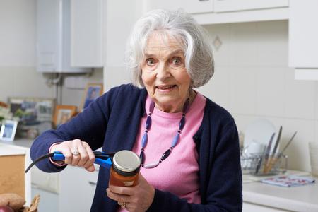 terapia ocupacional: Mujer mayor que toma saltar la tapa con ayuda de la cocina