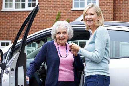 Buurvrouw Geven Hogere Vrouw Een lift in de auto Stockfoto