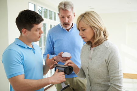demonstration: Security Consultant Demonstrating Alarm System To Mature Couple Stock Photo