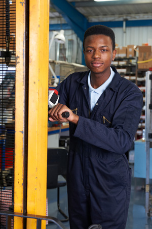 fork lift: Factory Worker Using Powered Fork Lift To Load Goods