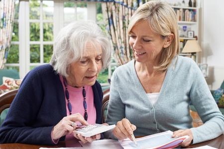 Female Neighbor Helping Senior Woman With Domestic Finances Stockfoto