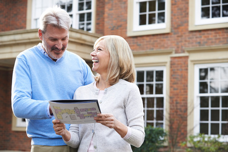 Mature Couple Standing Outside House Looking At Property Details 스톡 콘텐츠