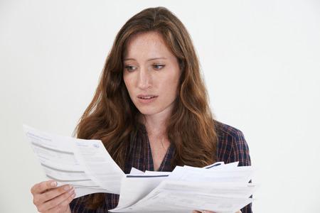 twenties: Studio Shot Of Worried Woman Looking At Bills