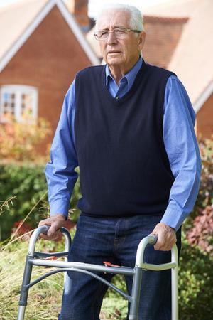 paraplegico: Deprimido hombre mayor que usa el marco caminar al aire libre Foto de archivo