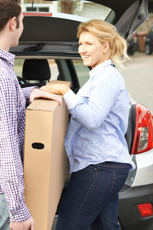 unloading: Couple Unloading New Television From Car Trunk
