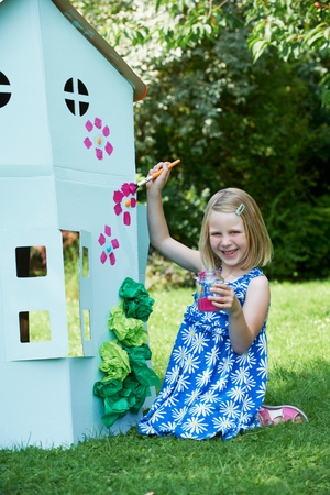 Young Girl Painting Home Made Cardboard House Stock Photo