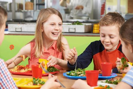 Groep leerlingen zitten aan tafel in school cafetaria eten lunch