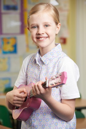 Girl Learning To Play Ukulele In School Music Lesson Stock Photo
