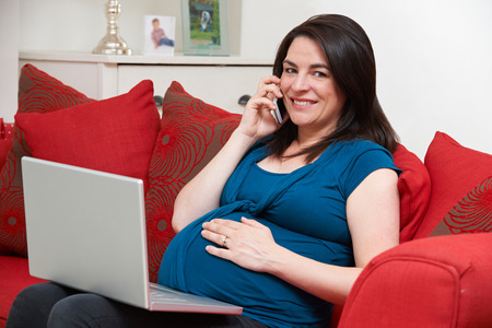 cellphones: Pregnant Woman Sitting On Sofa Using Laptop And Mobile Phone
