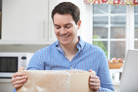online purchase: Happy Man Unpacking Online Purchase At Home Stock Photo