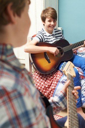 boys playing: Boys In Bedroom Playing Guitars Together