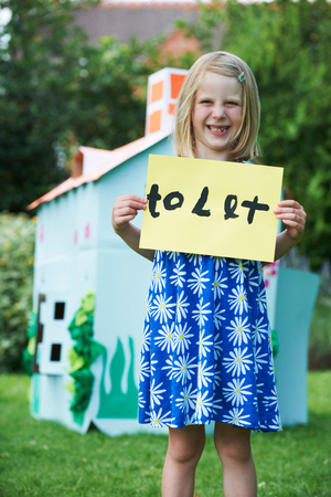 Little Girl Holding To Let Sign Outside Play House