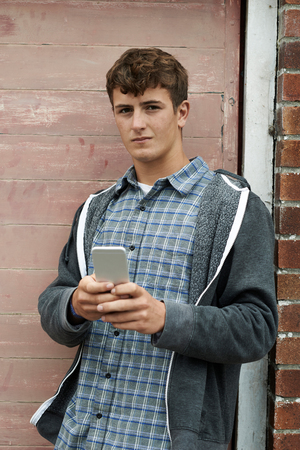 boy 16 year old: Teenage Boy Texting On Mobile Phone In Urban Setting