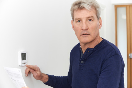Worried Mature Man With Bill Turning Down Central Heating Thermostat