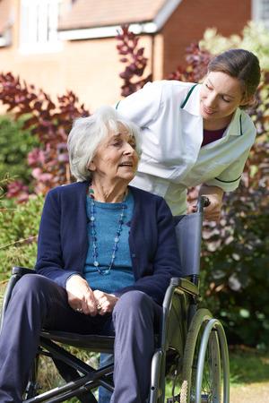 80s adult: Carer Pushing Senior Woman In Wheelchair
