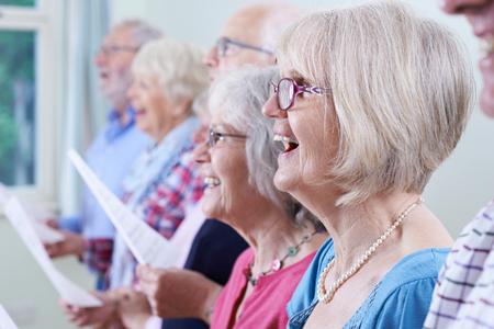 Grupo de personas mayores que cantan en coro Juntos