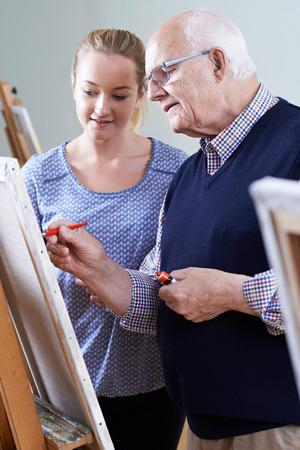 the elderly tutor: Senior Man Attending Painting Class With Teacher