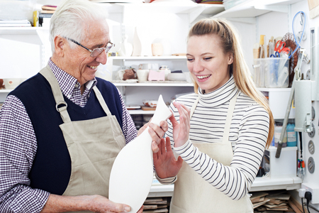 the elderly tutor: Senior Man With Teacher Looking At Vase In Pottery Class