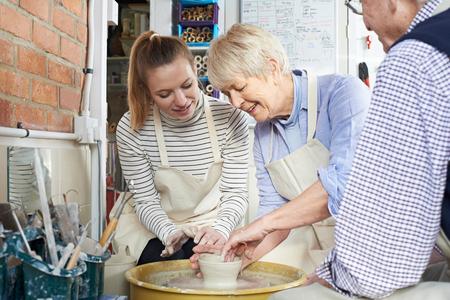 the elderly tutor: Seniors With Teacher In Pottery Class Stock Photo