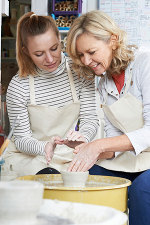 the elderly tutor: Mature Woman With Teacher In Pottery Class