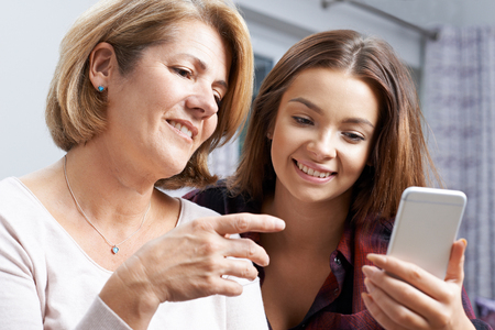 Teenage Daughter Showing Mother How To Use Mobile Phone