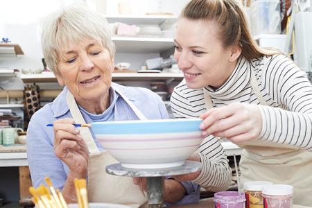the elderly tutor: Senior Woman Decorating Bowl With Teacher In Pottery Class