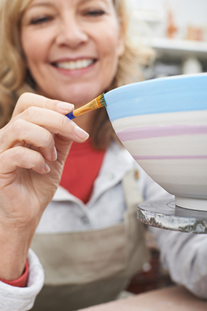 sculptor: Mature Woman Decorating Bowl In Pottery Class