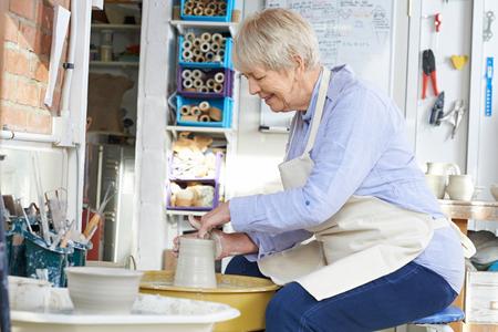 ceramica: Mujer mayor en el trabajo Rueda de la cerámica en estudio Foto de archivo