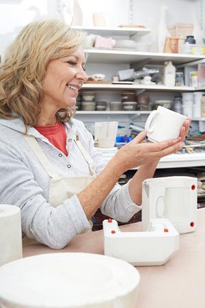 pottery: Mature Woman In Pottery Studio Casting Mug