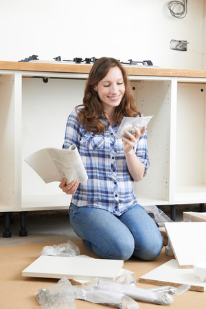 self assembly: Woman Assembling Units In New Kitchen Stock Photo
